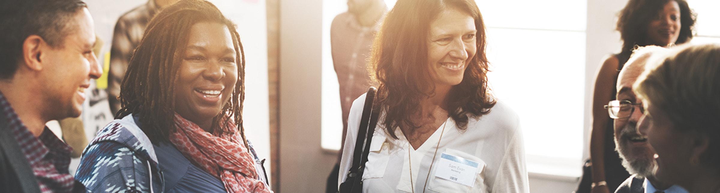 Immagine raffigurante in primo piano 2 donne sorridenti che dialogano con altre persone