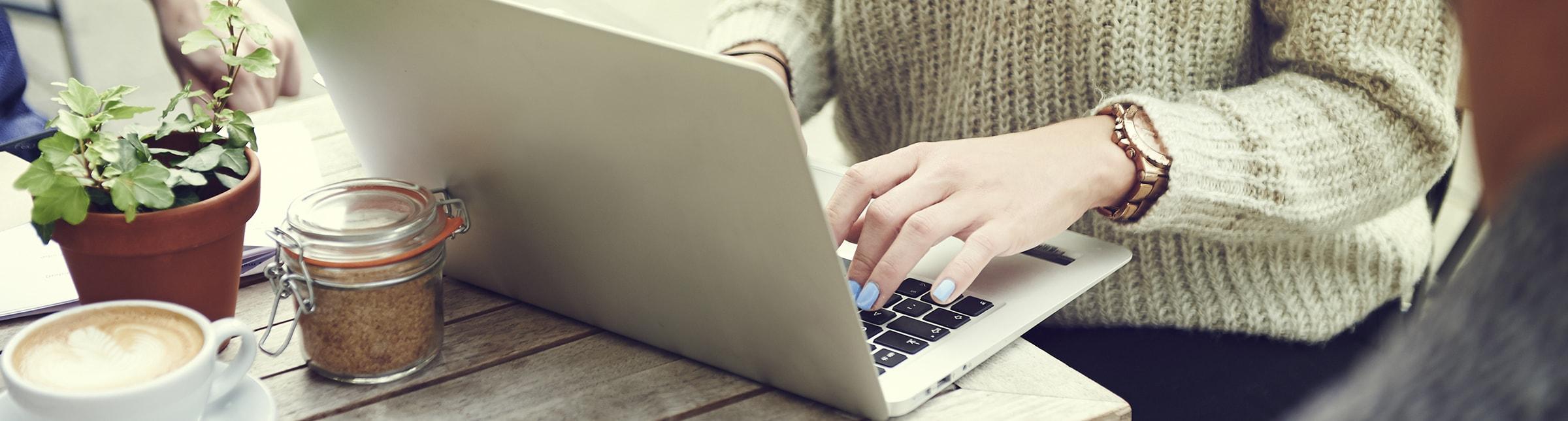 L'immagina rappresenta le mani di una donna giovane che sta digitando sulla tastiera di un portatile