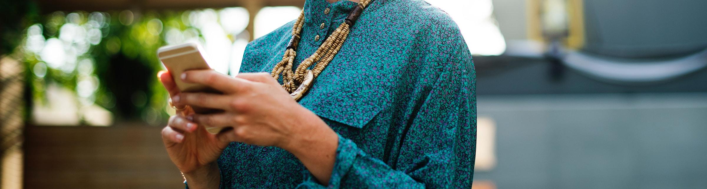 L'immagine rappresenta un primo piano di un busto di donna che tiene tra le mani un cellulare