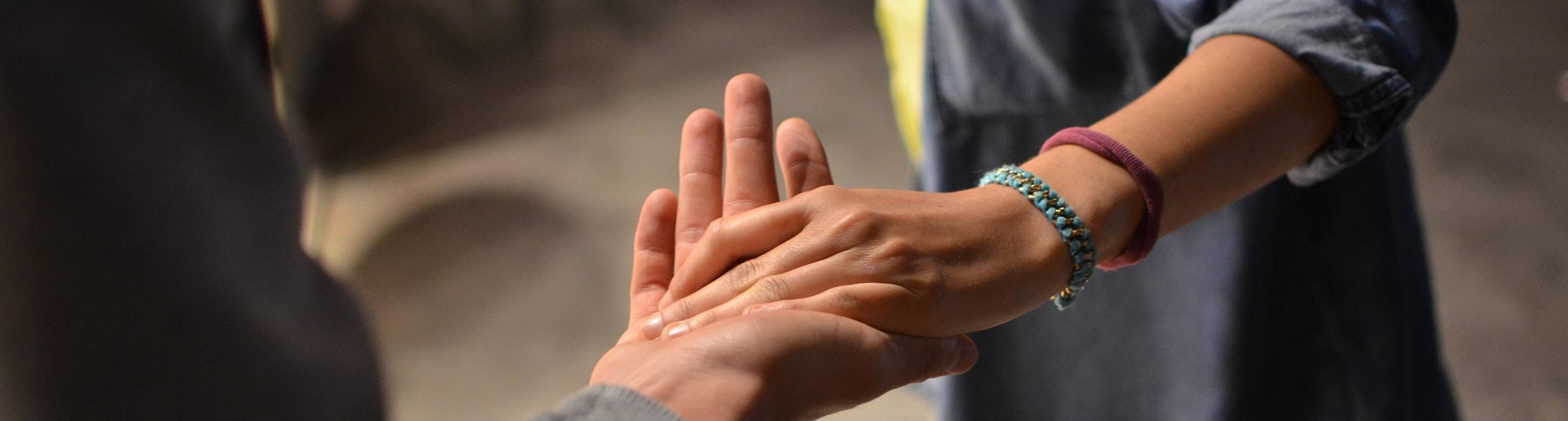 L'immagine rappresenta il primo piano della mano di un uomo tesa che accoglie la mano di una donna