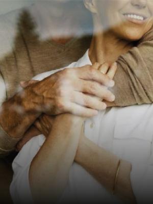 Una donna guarda oltre una finestra mentre un uomo l'abbraccia teneramente di spalle tenendole la mano