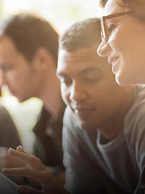 In un ambiente di lavoro una donna mostra un contenuto sul tablet a un ragazzo seduto accanto a lei