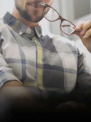 Dettaglio di un ragazzo con degli occhiali in mano che tiene vicino alla bocca