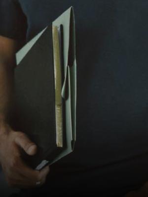 Un ragazzo con una cartellina e un'agenda nera sotto braccio