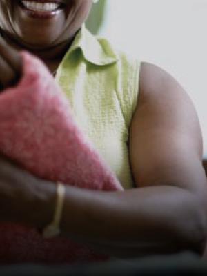Donna di origine africana sorridente in una stanza molto luminosa piega con cura un tessuto colorato