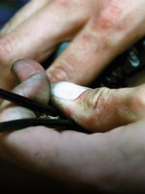 Primo piano di mani operose che stringono un cavo nero