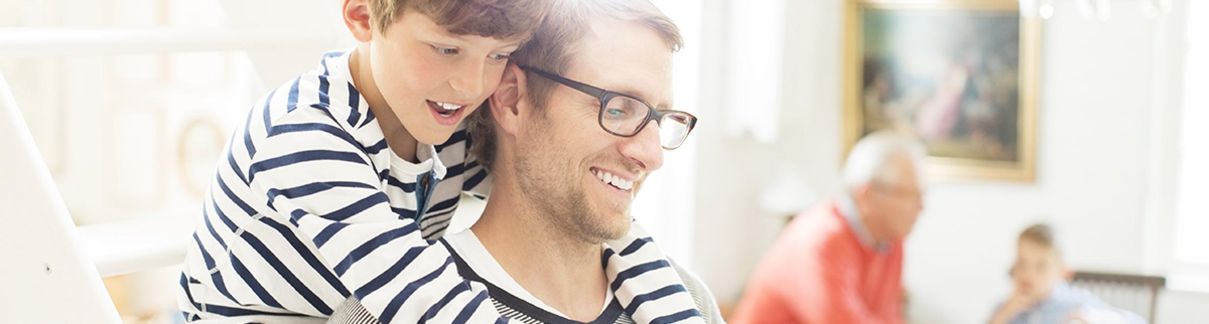 Papà giovane che viene abbracciato alle spalle dal proprio figlio