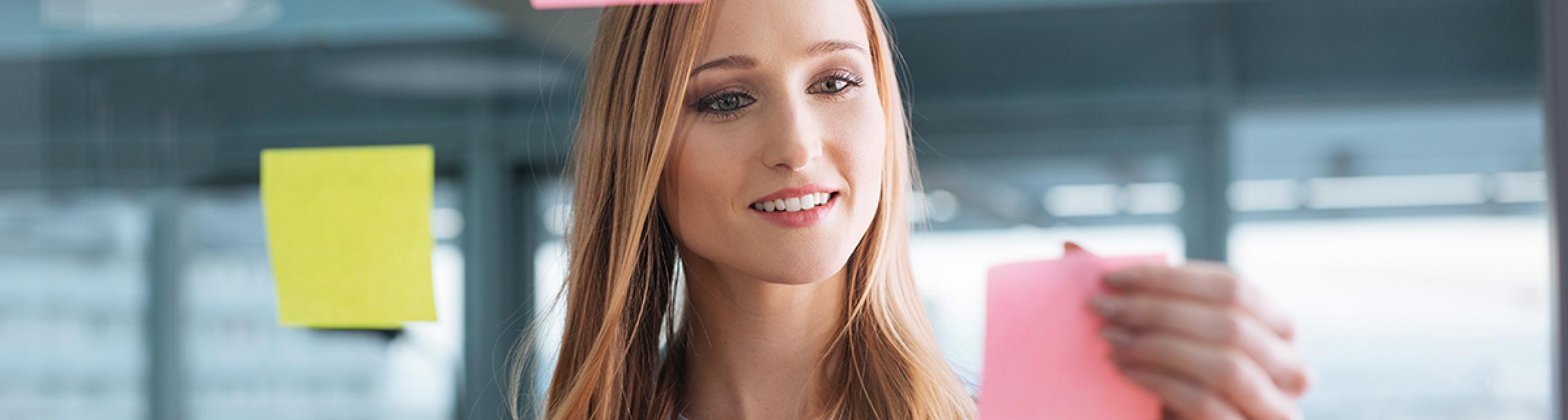 Primo piano di una ragazza attacca dei post-it su di un vetro davanti a lei