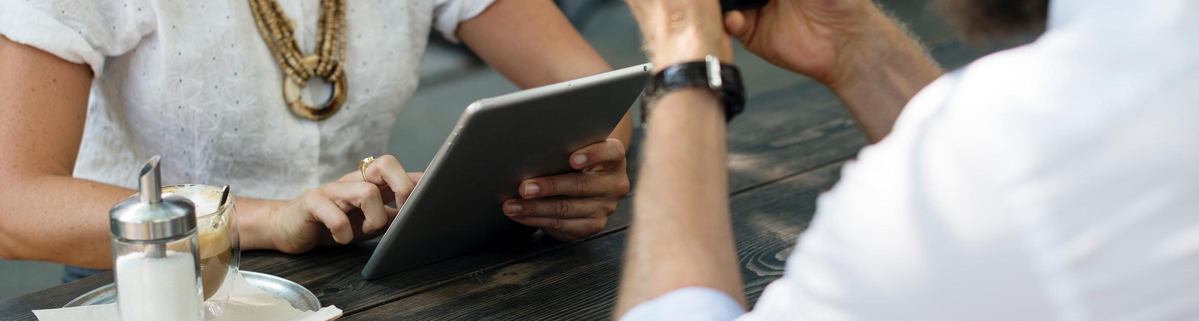 Un ragazzo seduto ad un tavolo con in mano un cellulare, di fronte una ragazza con un tablet