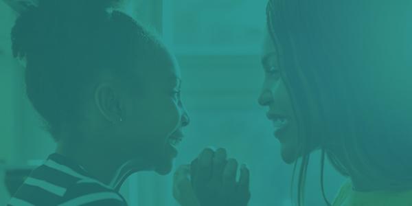 Primo piano sullo sguardo sorridente tra una donna e una bambina che si tengono la mano