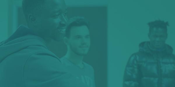 Un primo piano sul sorriso di un ragazzo che si trova in una sala insieme ad altri due ragazzi