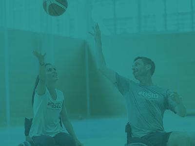Due persone, una ragazza e uomo, sulla sedia a rotelle che stanno giocando a basket