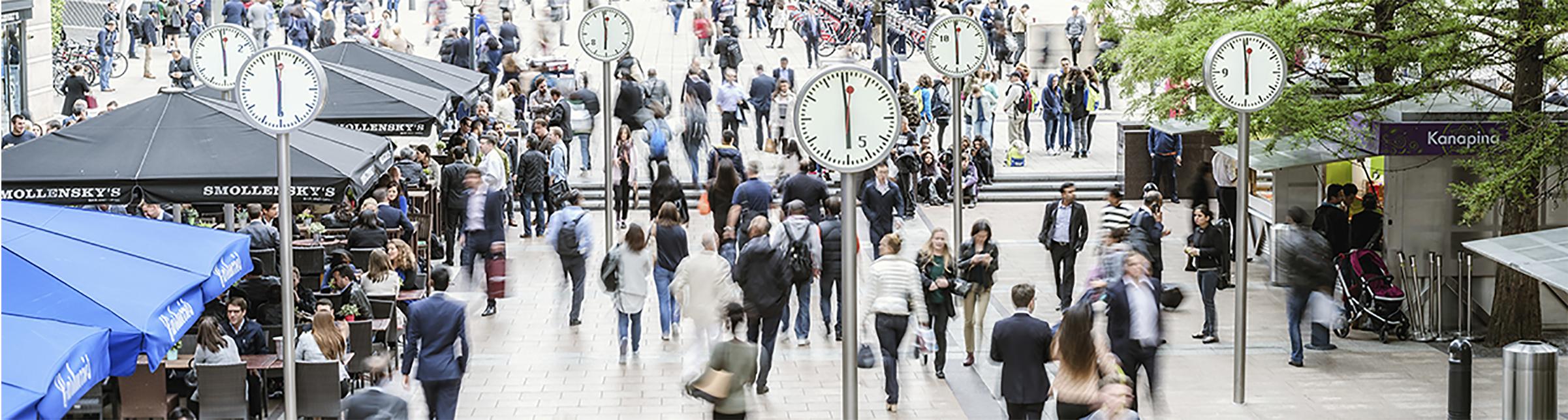 Piazza affollata con gli orologi che segnano mezzogiorno.