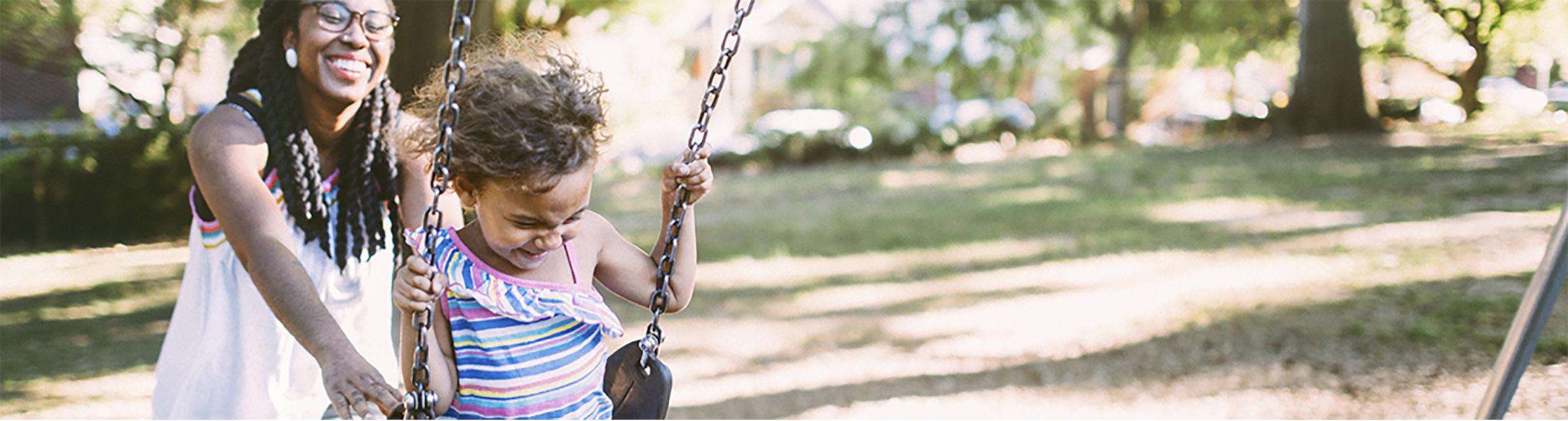 Una donna di colore che spinge sull'altalena una bambina di colore all'interno di un parco cittadino