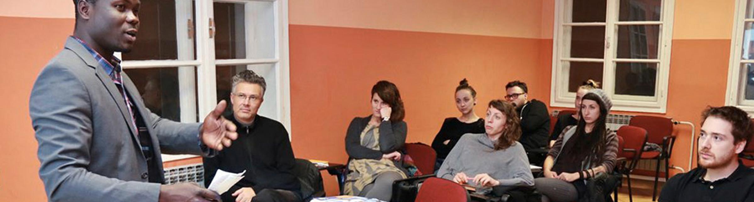 In un'aula di formazione un insegnante di origine africana parla ad un gruppo di persone