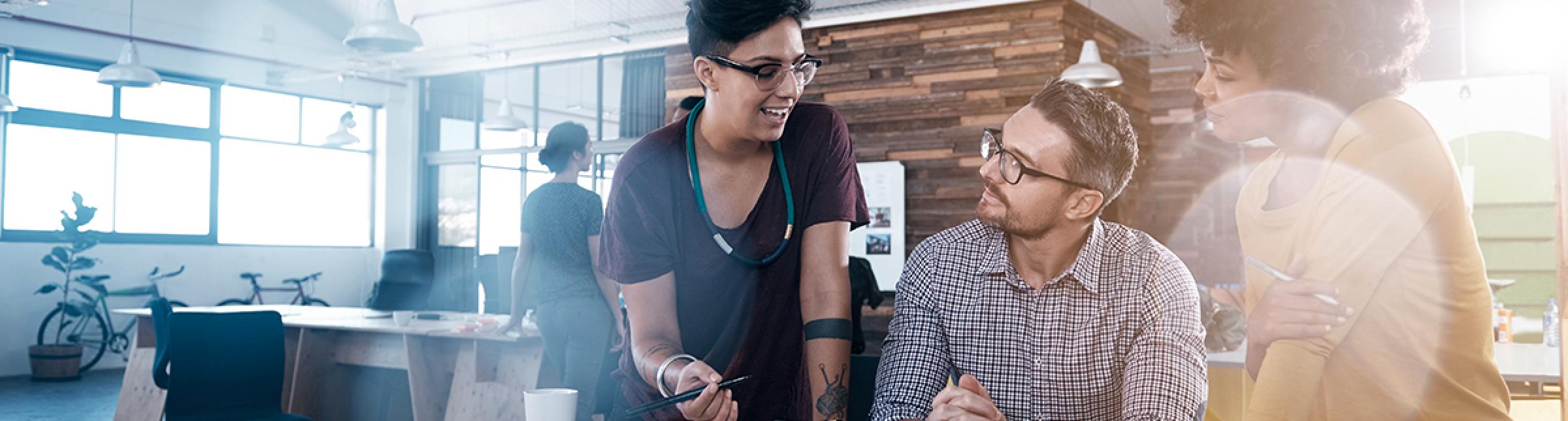 Immagine raffigurante 3 giovani, 2 donne e un uomo, che lavorano ad un progetto intorno ad un tavolo