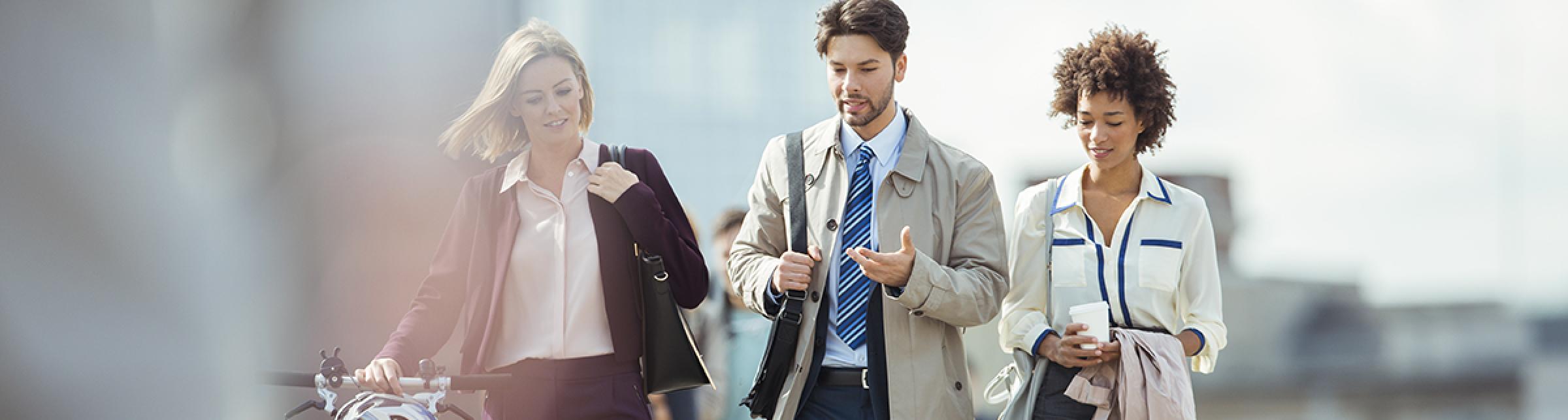 Un uomo e due donne, in abiti da ufficio, passeggiano per strada discorrendo tra loro.