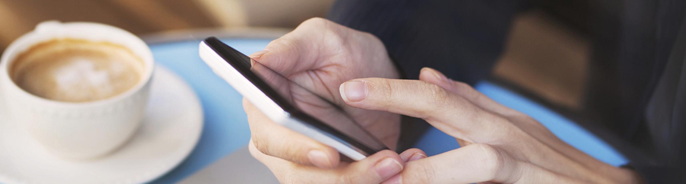 Immagine che rappresenta una persona che sta utilizzando un cellulare seduta ad un tavolo