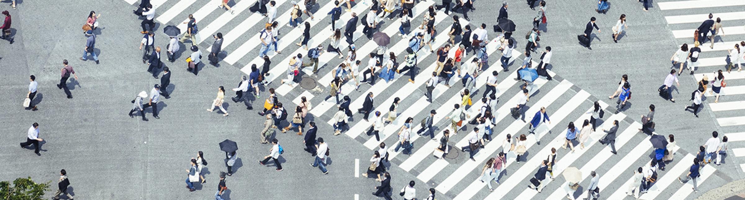 Un incrocio metropolitano con più attraversamenti pedonali e persone che li percorrono