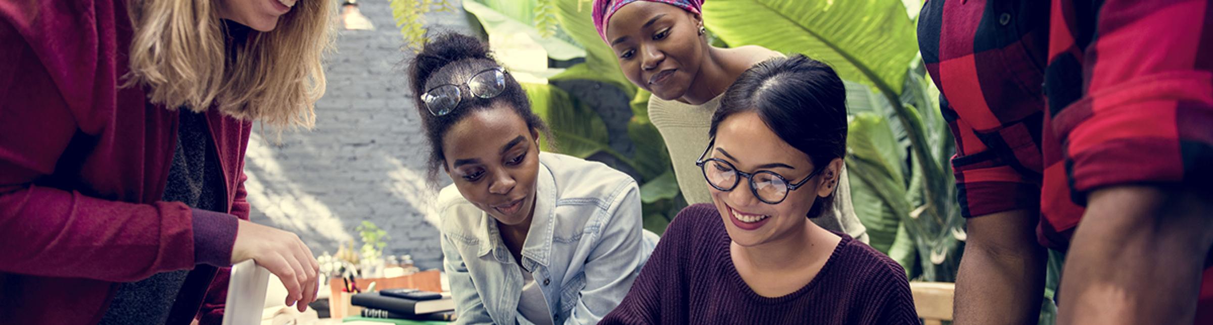 Un team di 5 persone di origine multietnica, che lavorano ad un tavolo