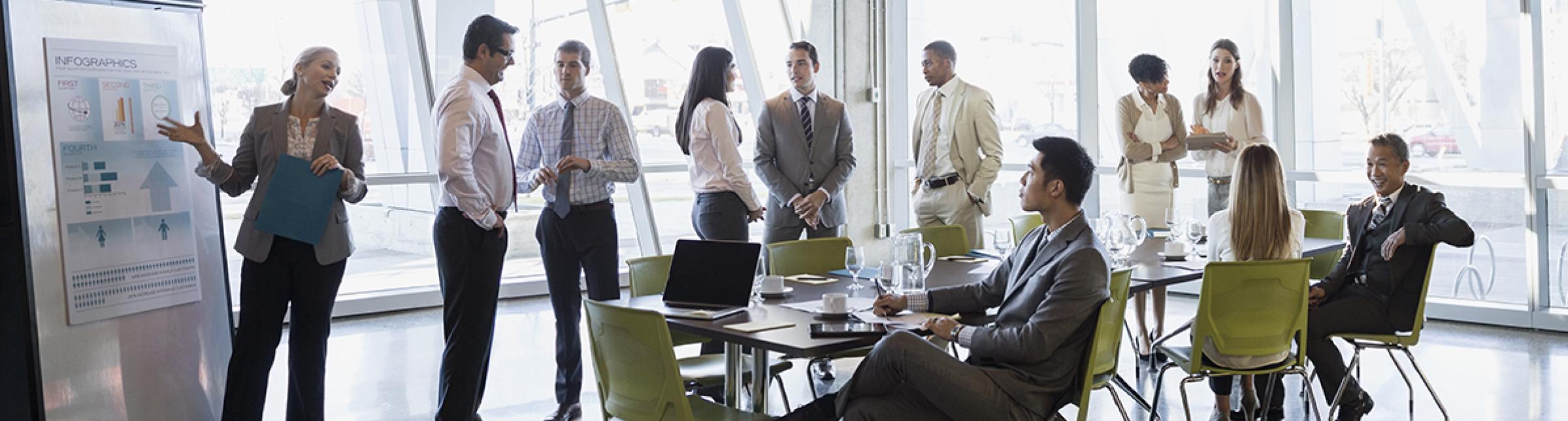 Colleghi in una sala riunioni. Alcuni in piedi, altri seduti, una di loro intenta a spiegare un grafico