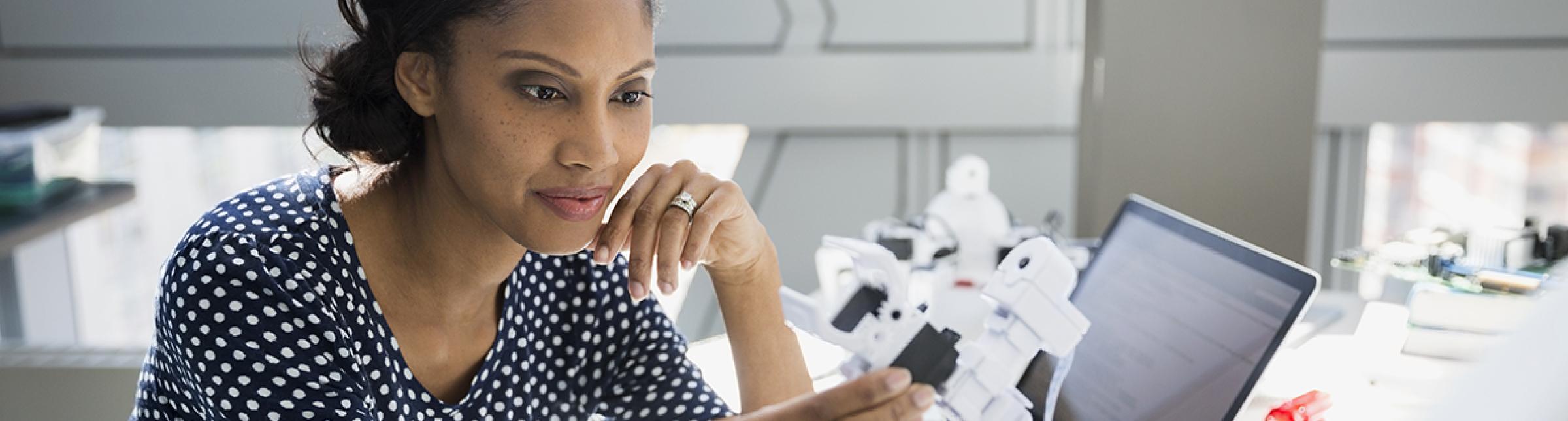 Una donna seduta in una postazione d'ufficio con, tra le mani, un prototipo di robot